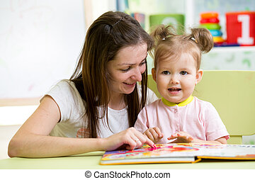 mother and child girl read a book at home