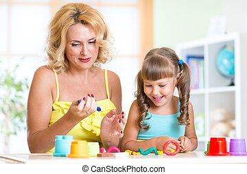 mother and child have fun with colorful play clay toys