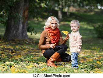 Mother and child having fun in autumn park