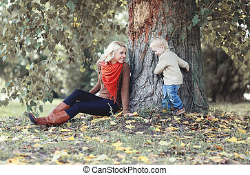 Mother and child having fun in autumn