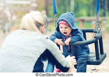 mother and child having fun in swing at playground