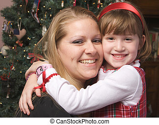 Mother and Child Hug in Front of a Christmas Tree.