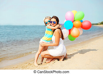 Mother and child hugging with colorful balloons on beach near sea