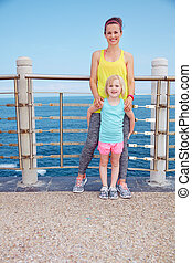 Mother and child in fitness outfit standing on embankment
