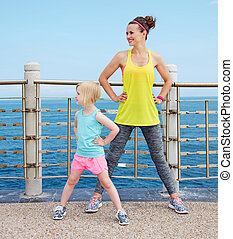 Mother and child in fitness outfit stretching on embankment...