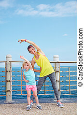 Mother and child in fitness outfit stretching on embankment