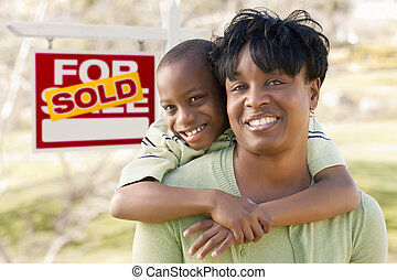 Mother and Child In Front of Sold Real Estate Sign