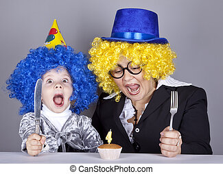 Mother and child in funny wigs and cake at birthday. Studio shot.