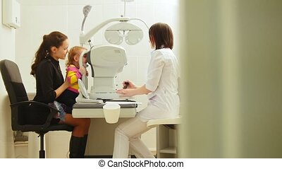 Mother and child in the ophthalmologist's room- optometrist in clinic checking little child's vision
