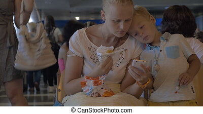 Mother and child in waiting room of the airport - Mother and...