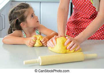 Mother and child kneading dough - Mother show her child...