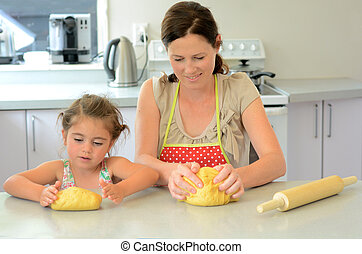 Mother and child kneading dough