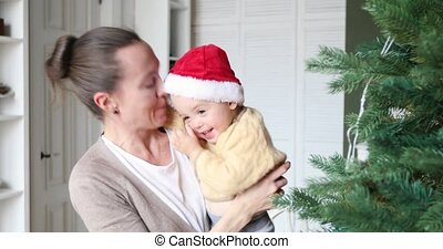 Mother and child laugh at the Christmas tree