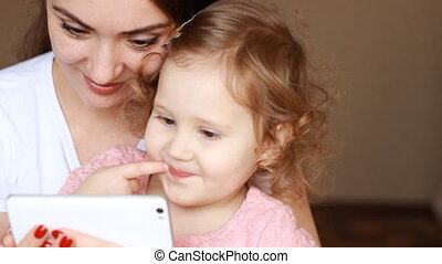 Mother and child looks at the phone screen and plays...