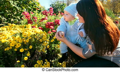 mother and child near a flowerbed in a sunny autumn day
