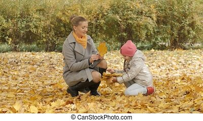 mother and child on a background of yellow fallen leaves in the autumn in the forest