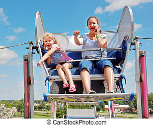 mother and child on ferris wheel - Mom on cell phone with...