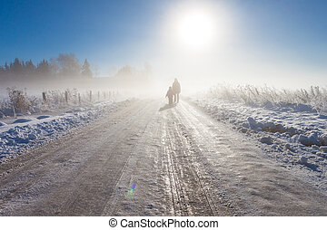 Mother and child on foggy snow farm road