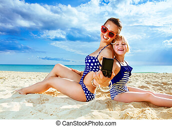 mother and child on seashore with digital camera taking selfie