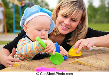 mother and child  play in sandbox