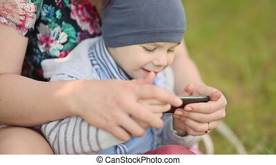 Mother and child playing a game with phone on grass