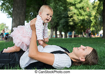 mother and child playing in the park on the grass
