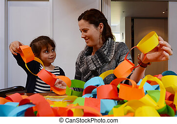 Mother and child preparing a handcraft decoration together -...