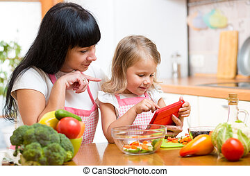 Mother and child preparing vegetables together at kitchen and lo