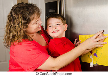 Mother and child putting up boy's art on family refrigerator at home