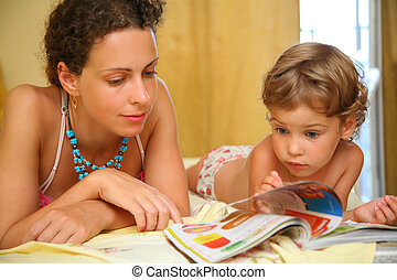 Mother and child read magazine