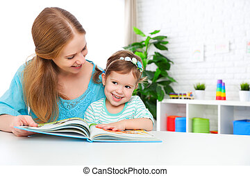 mother and child reading  book at home