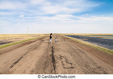 Mother and child running barefoot on a long, empty road