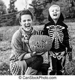 mother and child showing Halloween pumpkin Jack O'Lantern