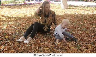 Mother and child sit on leaves in the park