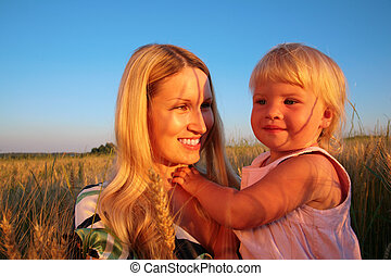 Mother and child  sit on wheat field