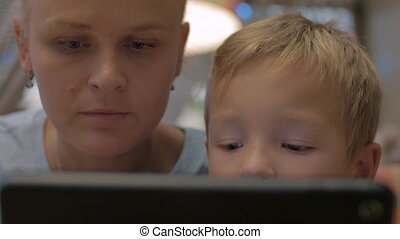 Mother and child spending time on touch pad using - Close-up...
