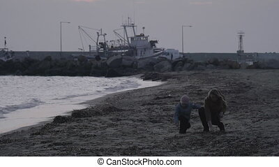 Mother and child throwing stones in the sea