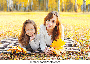 Mother and child together with yellow maple leafs in autumn day