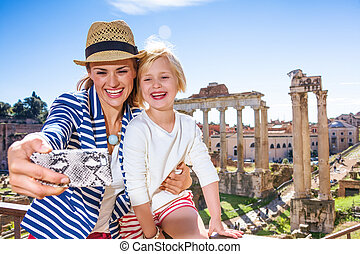 mother and child tourists in Rome taking selfie with phone