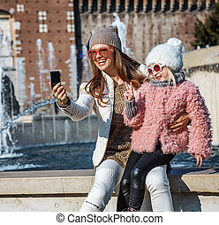 mother and child travellers with digital camera taking selfie