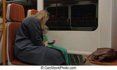 Mother and child using cell in moving subway train