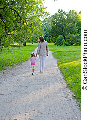 Mother and child walk in the park. Back view