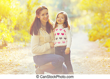 Mother and child walking in sunny autumn day