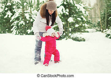 Mother and child walking in the winter park