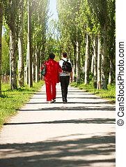 Mother and child walking together in summer city park