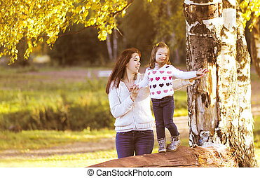 Mother and child walks in the autumn day