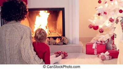 Mother and child warm up by the fireplace with a white...