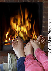 Mother And Child Warming Bare Feet By Fire