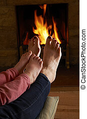 Mother And Child Warming Feet By Fire