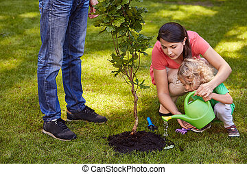 Mother and child watering tree